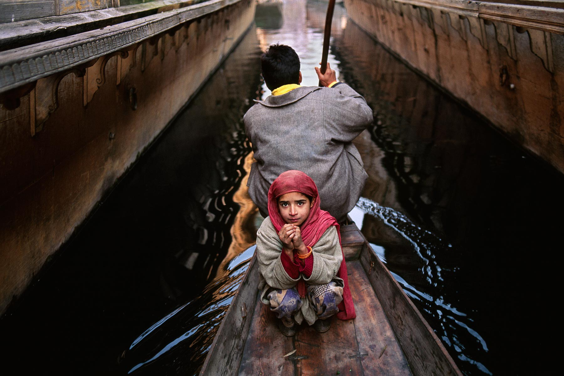 KASHMIR-10015, 1996, final print_milan A girl and her father go to the floating vegetable market in their shikara in Srinagar. Much of the city is surrounded by Dal Lake, where thousands of people use these canoe-like boats to go to and from their homes. Srinagar, Kashmir, India, 1996. Magnum Photos, NYC5946, MCS1999005 K200.